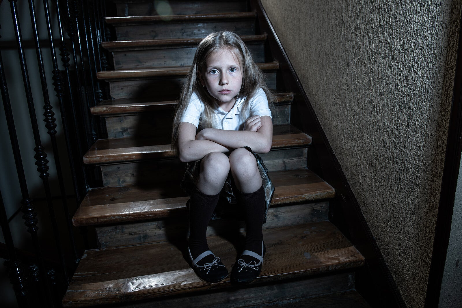Niña sentada en la escalera de casa con el uniforme de la escuela porque no quiere ir al colegio.