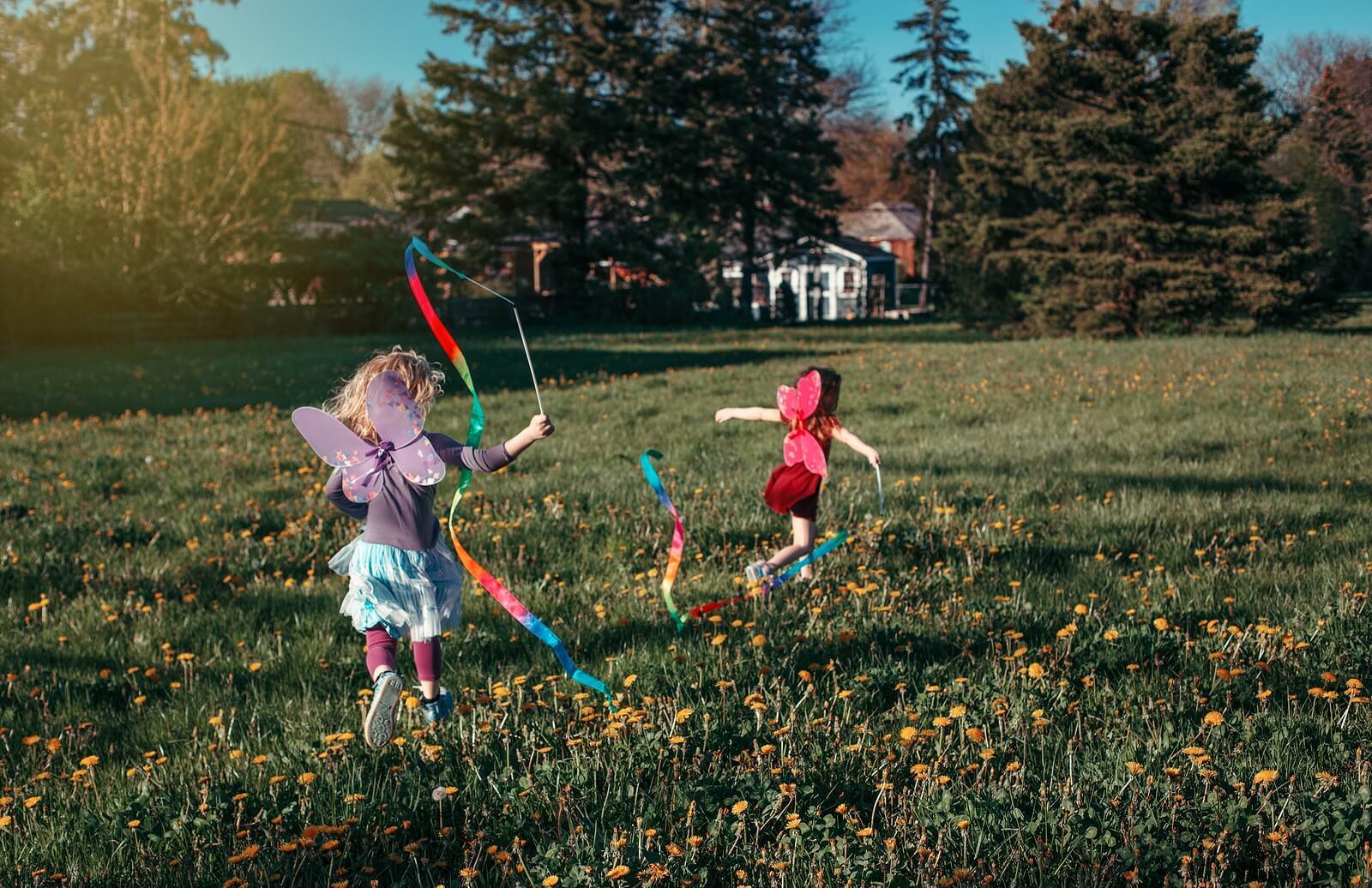Niñas corriendo y jugando por el parque disfrazadas de hadas.