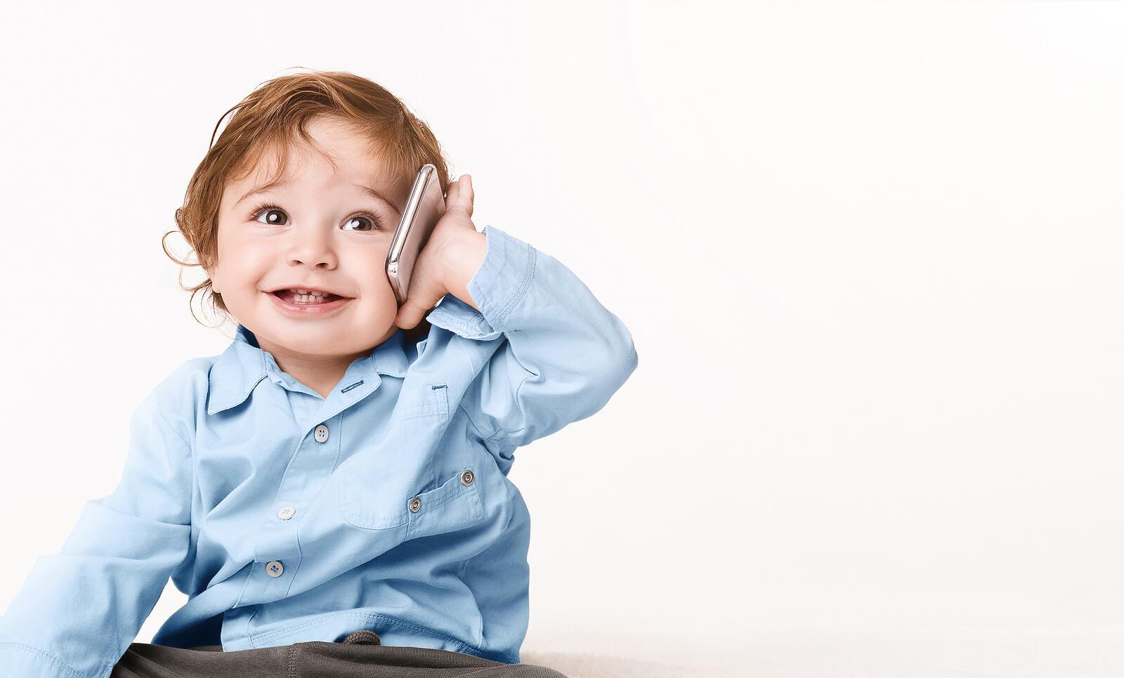 Nino pequeño diciendo sus primeras palabras por teléfono.