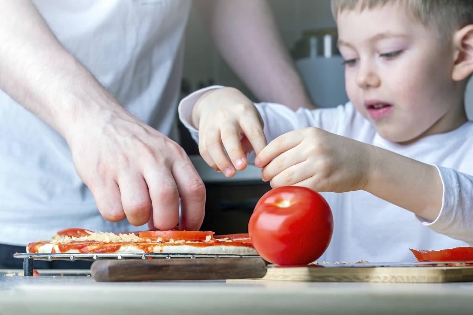 Niño ayudando a su padre a cocinar una pizza.