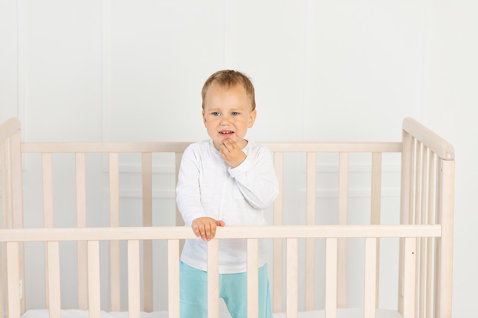 Niño llorando en su cuna tras pasar el bebé a su propia habitación.
