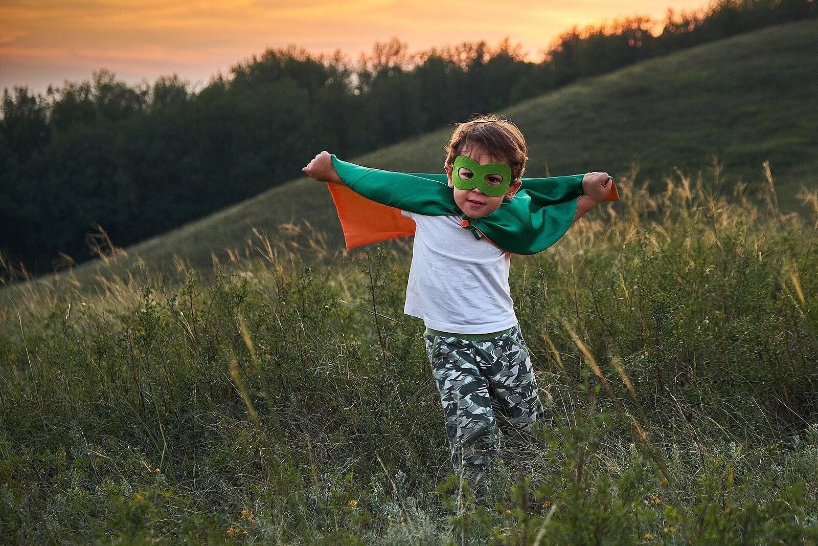 Niño disfrazado de superhéroe en el campo para desarrollar su imaginación y creatividad.
