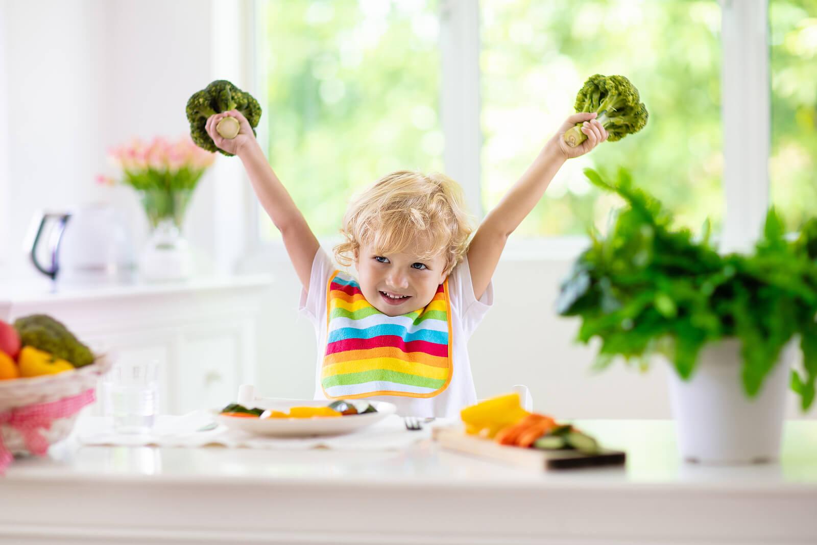 Niño feliz porque va a comer frutas y verduras.