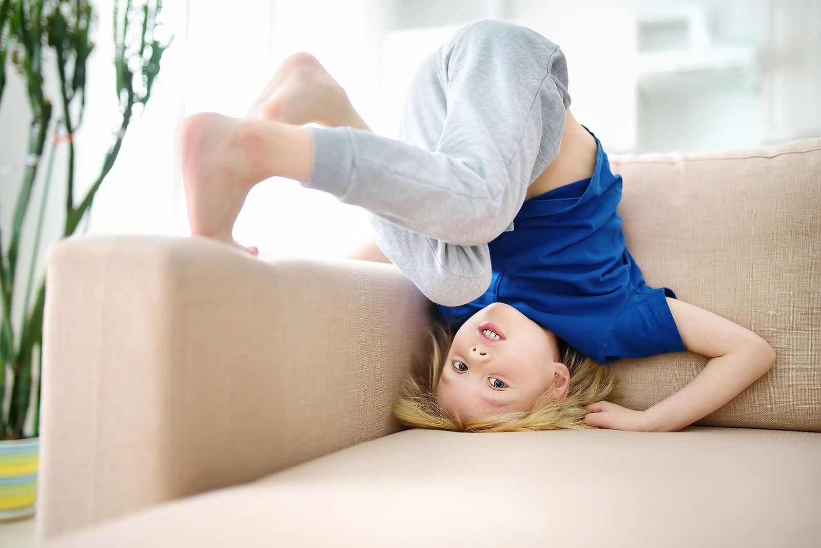Niño haciendo la voltereta en el sofá porque forma parte de los niños impulsivos.