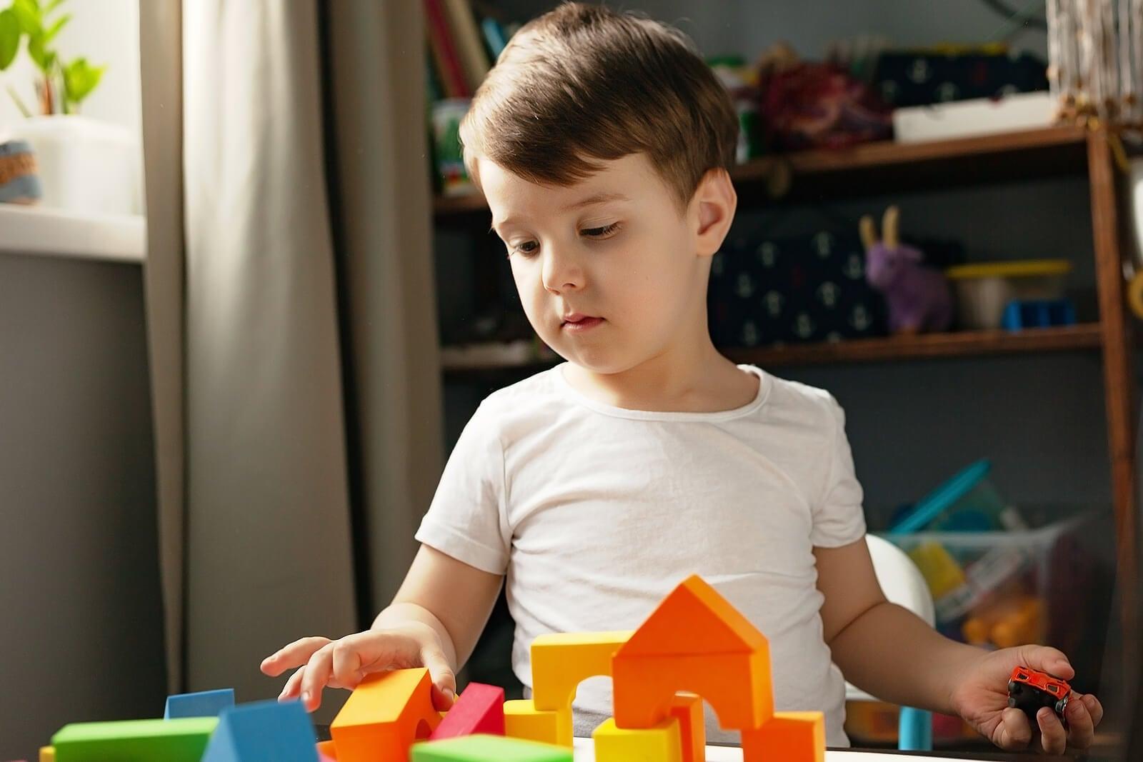 Niño jugando con los bloques de construcción pero sin querer recogerlos.
