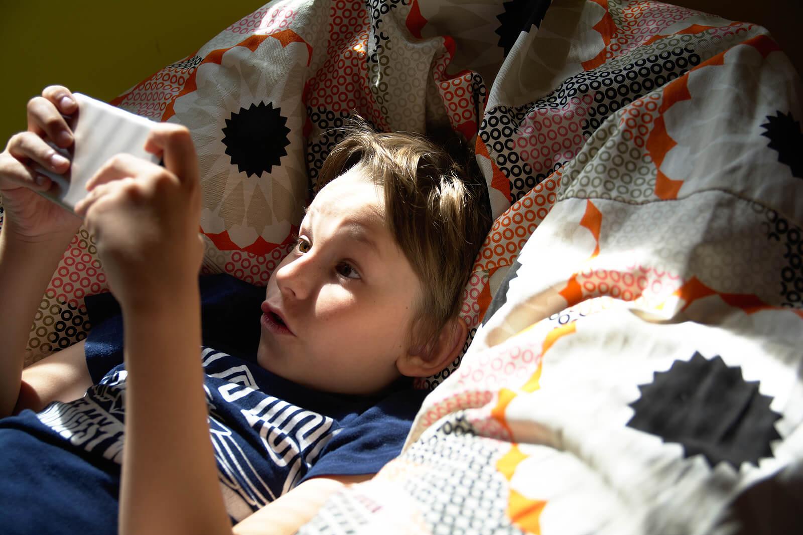 Niño jugando en la cama con el móvil.