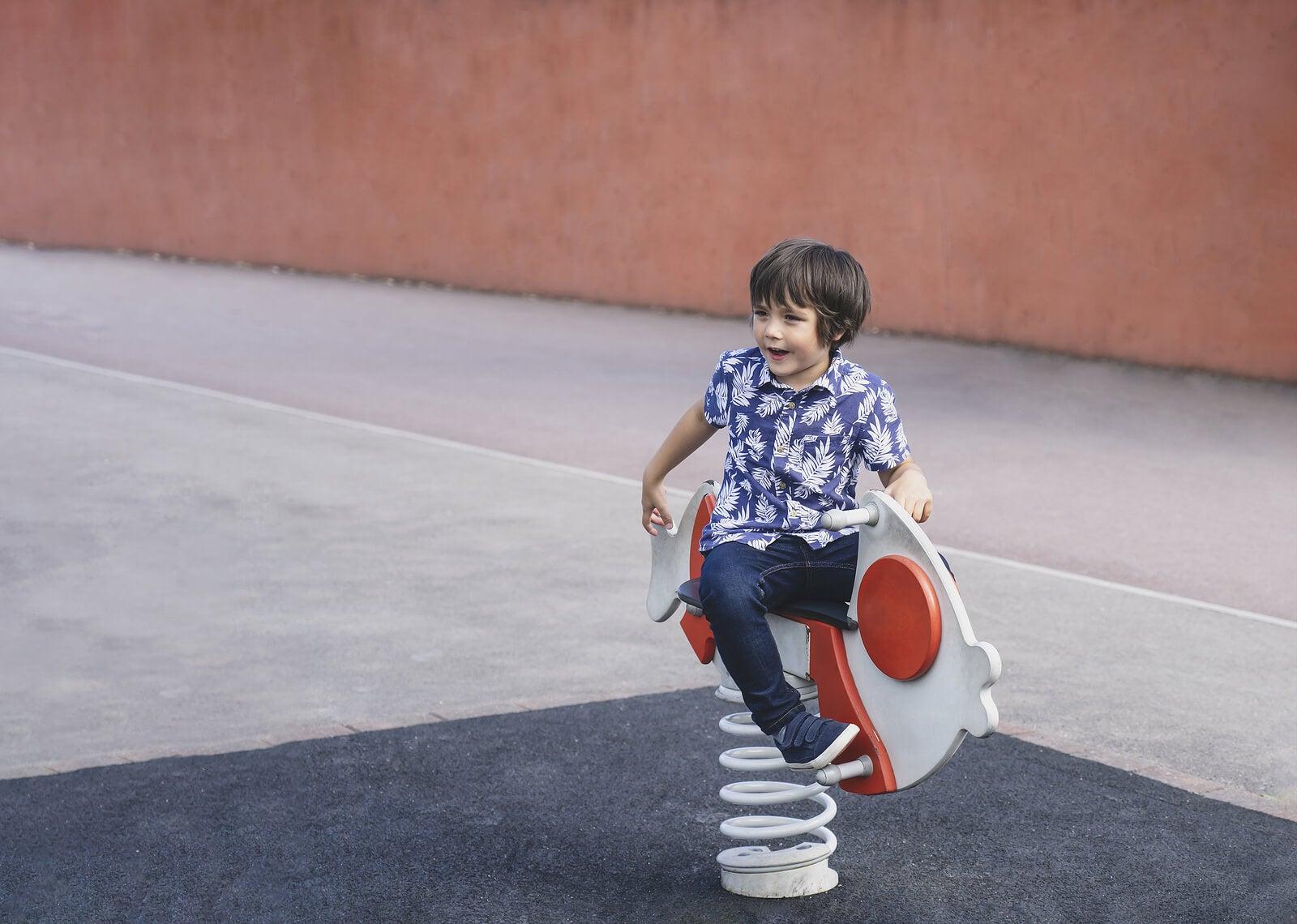 Niño jugando solo en un columpio del parque.