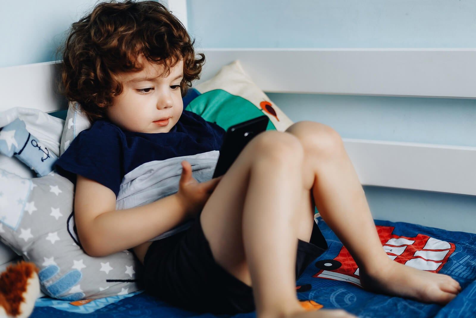 Niño jugando con el móvil porque no es consciente de que el teléfono móvil no es un juguete para niños.