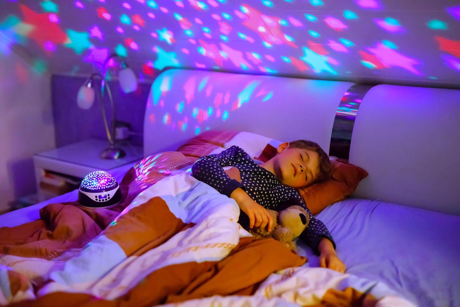 Niño durmiendo tranquilo con luz tenue y música relajante.