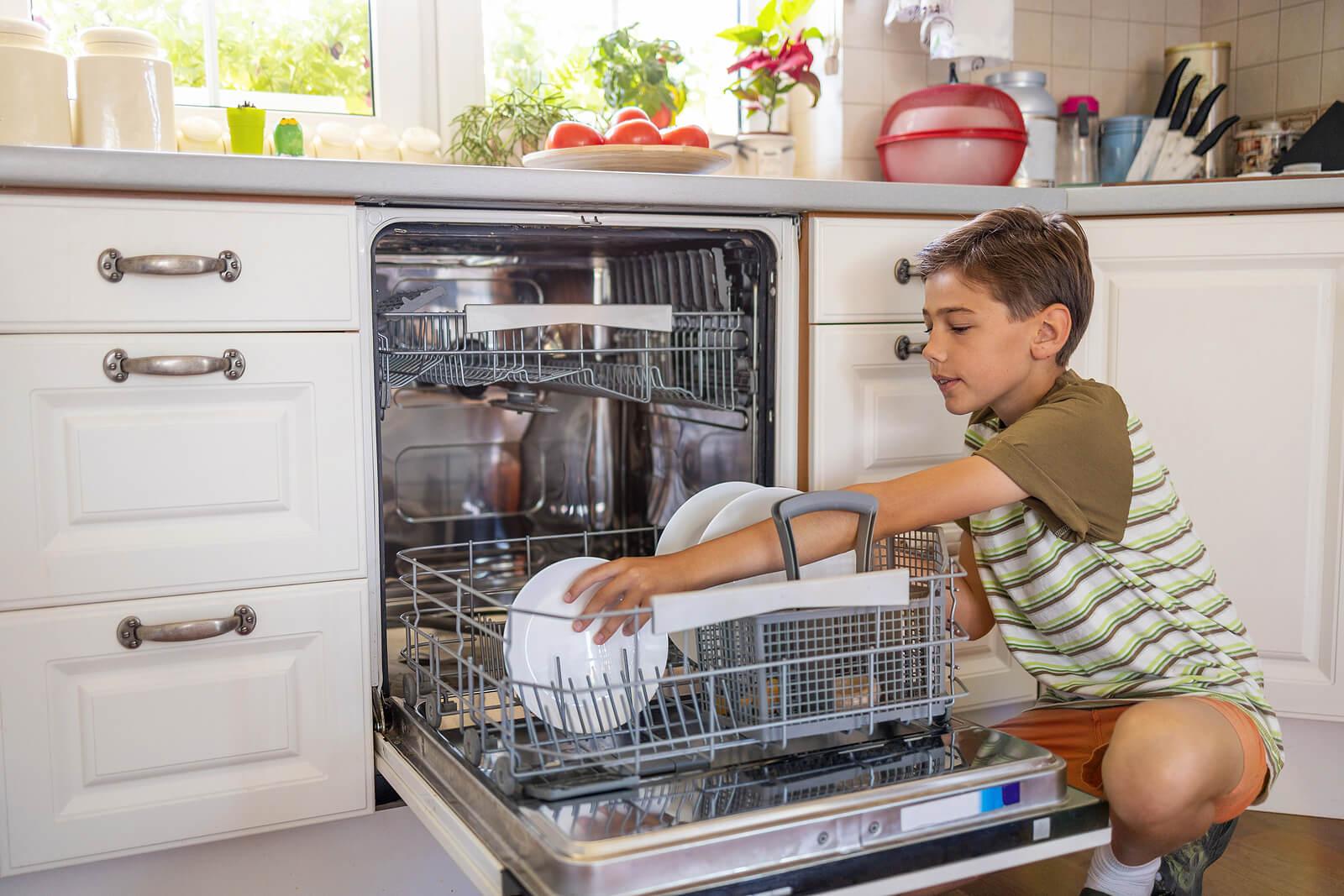 Niño metiendo los platos sucios en el lavavajillas para fomentar la responsabilidad en niños.