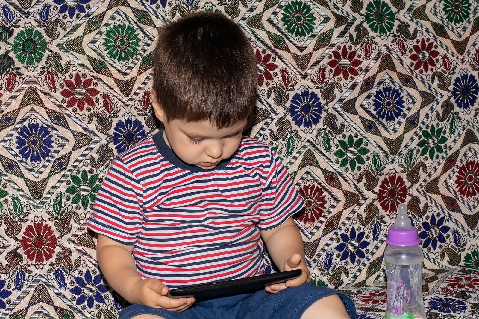 Niño viendo películas en el móvil porque es incapaz de desconectar de las pantallas.