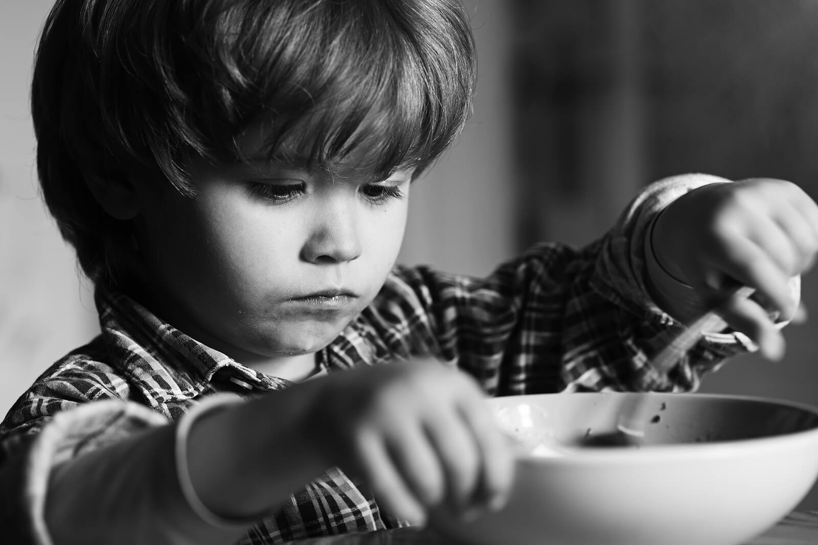 Niño preocupado mientras come por miedo a atragantarse.