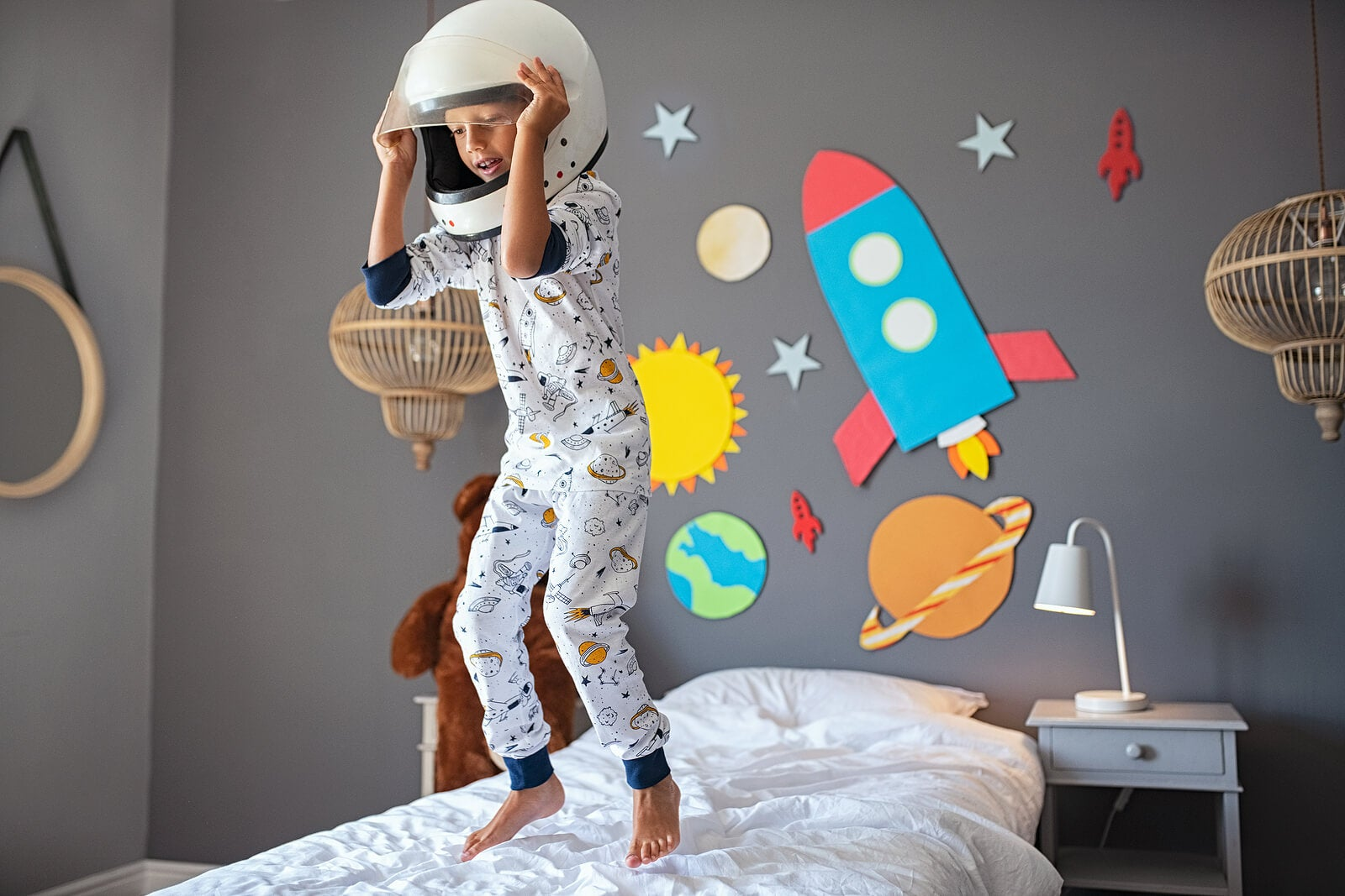 Niño saltando en la cama disfrazado de astronauta.