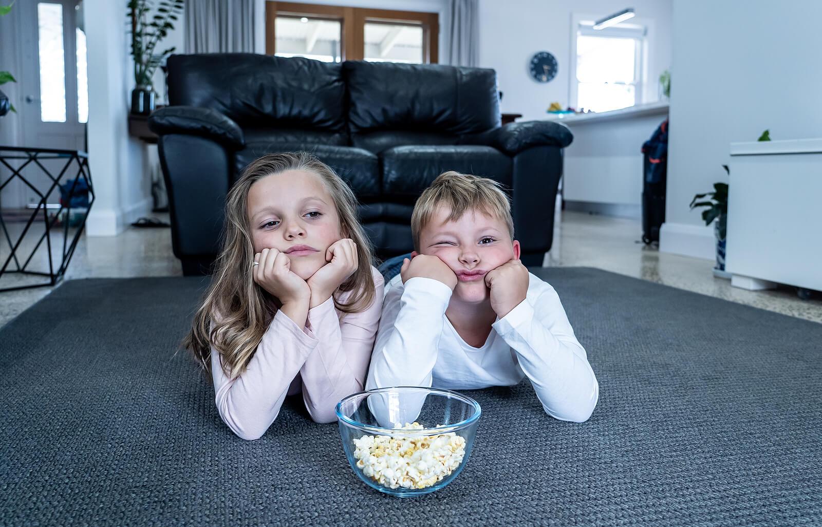 Niños que se aburren en vacaciones viendo una película.