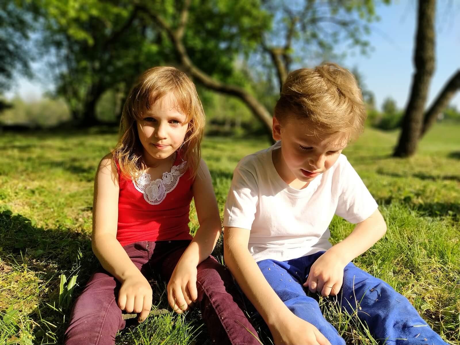 Niños sentados sin hablar porque al hijo le cuesta hacer amgios.