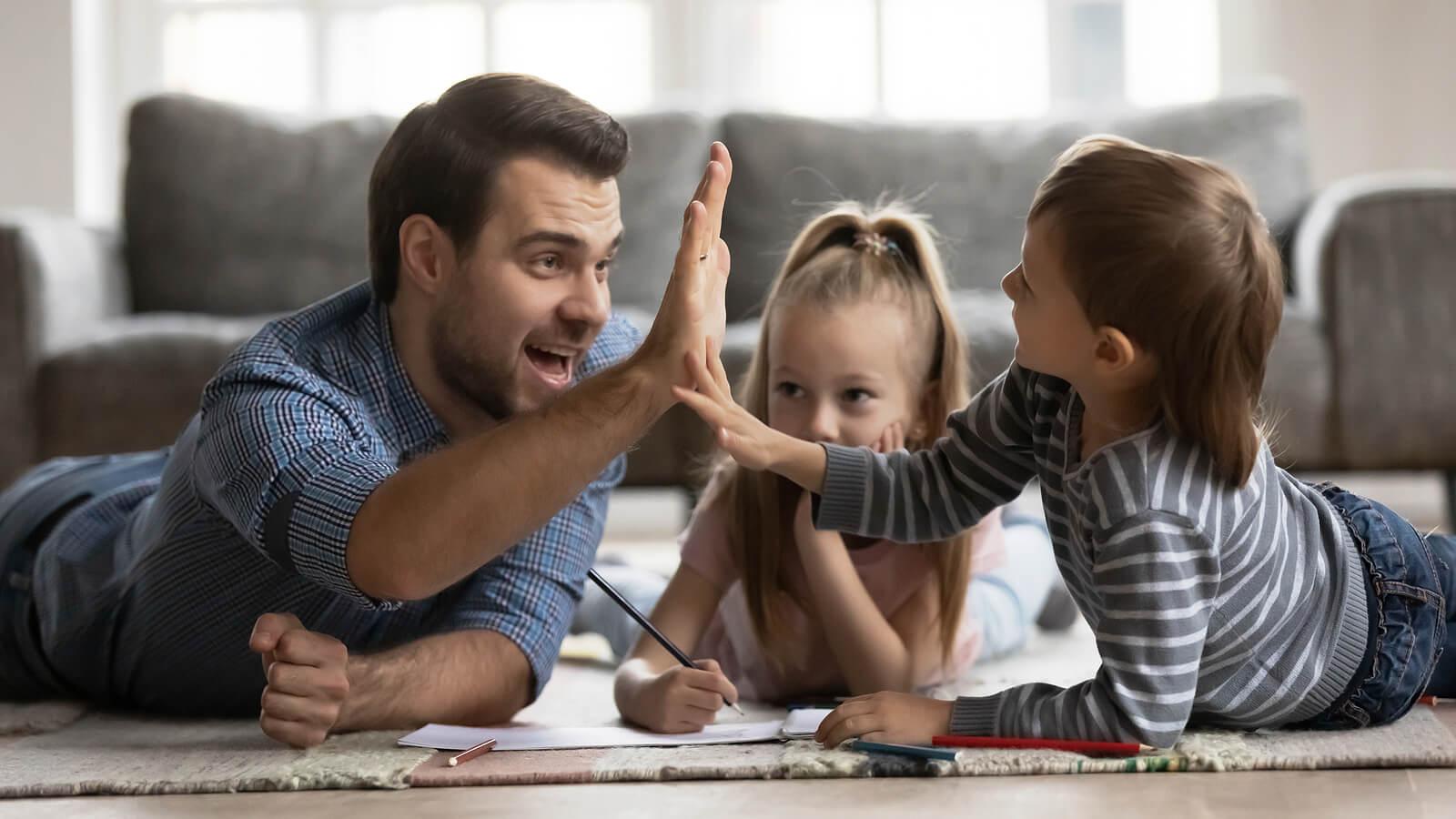 Padre chocando la mano con su hijo como parte de usar los elogios como premios y recompensas para niños.