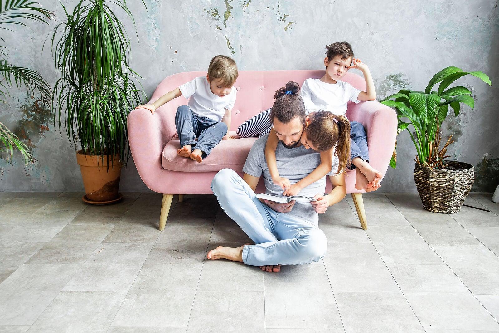 Padre leyendo a sus hijos en voz alta un cuento.