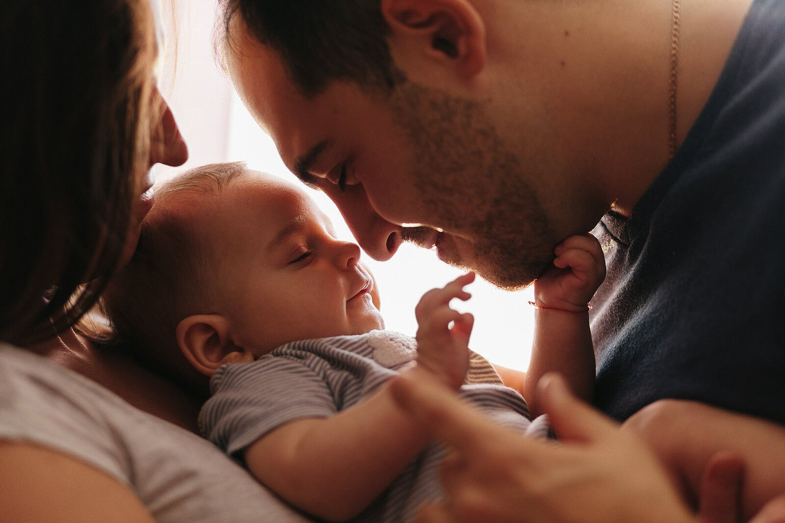 Padres abrazando a su bebé para crean un vínculo y conectar con él.
