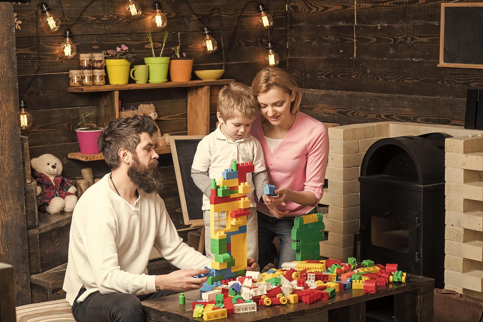 Padres jugando con su hijo con las piezas de construcción de LEGO Education.