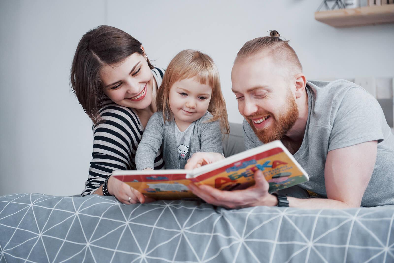 Padres leyendo cuentos infantiles para trabajar la gestión de la ira a su hija.