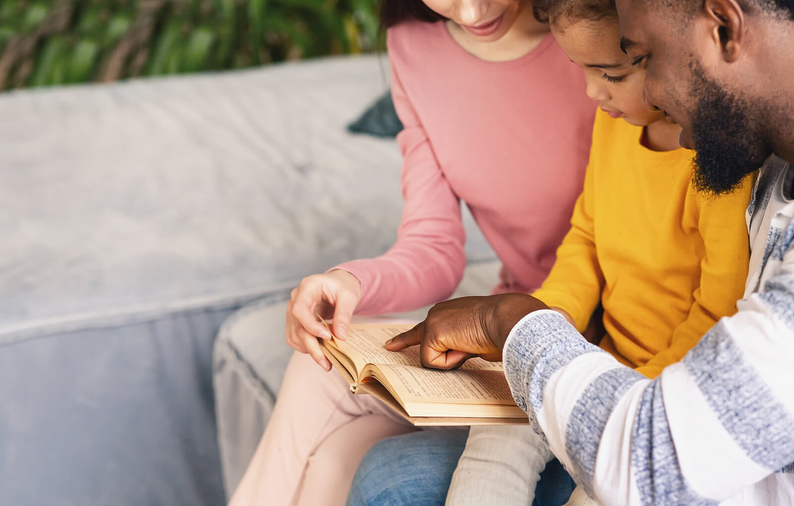 Padres leyendo en voz alta con su hijo.