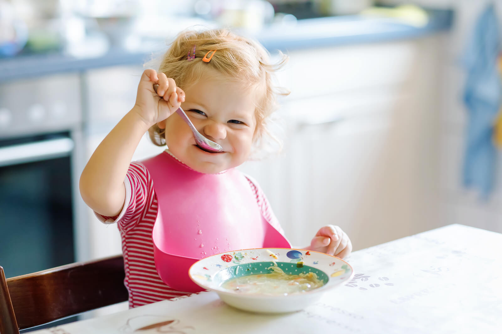 Bebé comiendo solo con cuchara une dieta con gluten.