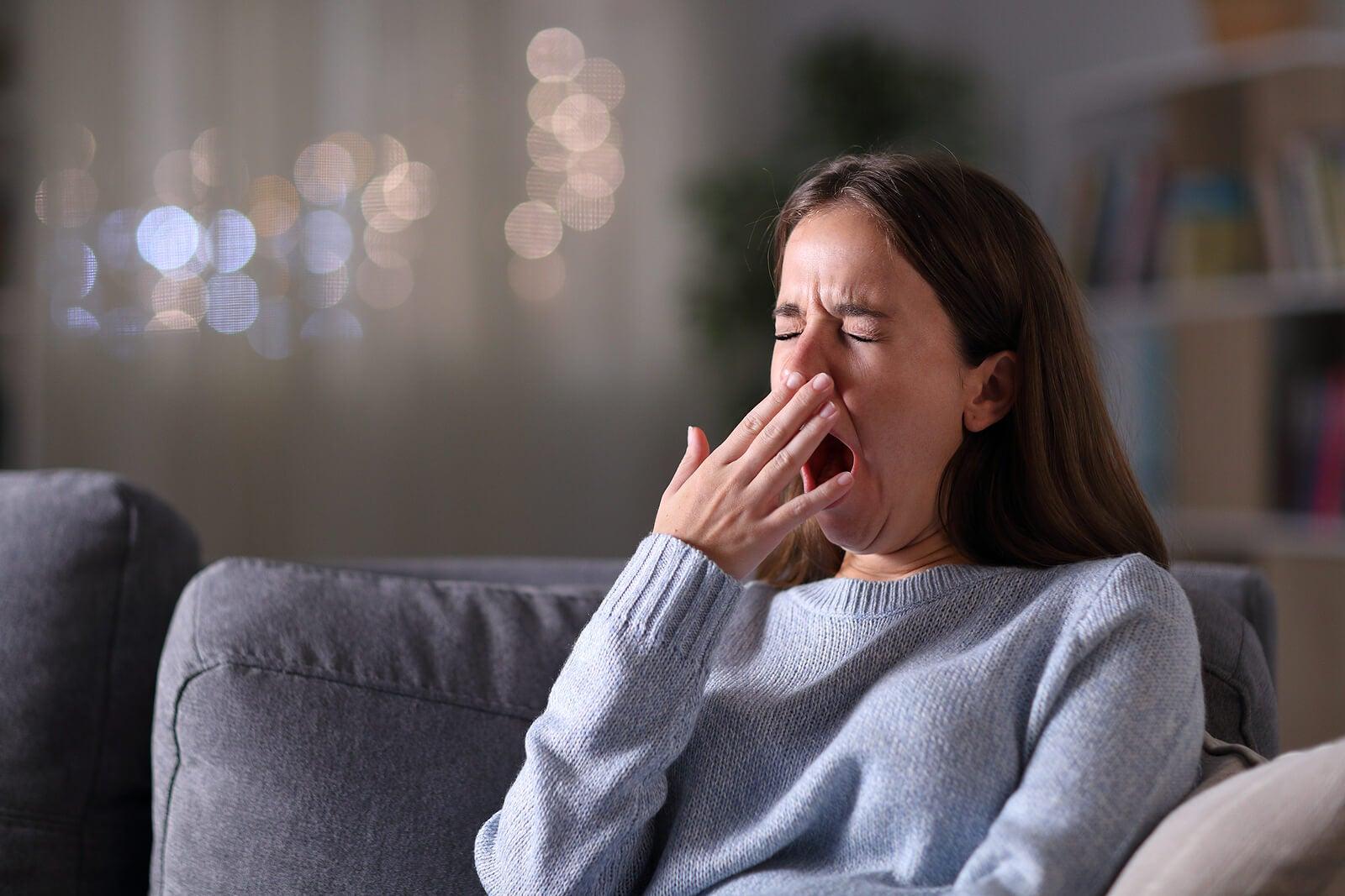 Chica adolescente bostezando debido a que sufre el síndrome de fatiga crónica.