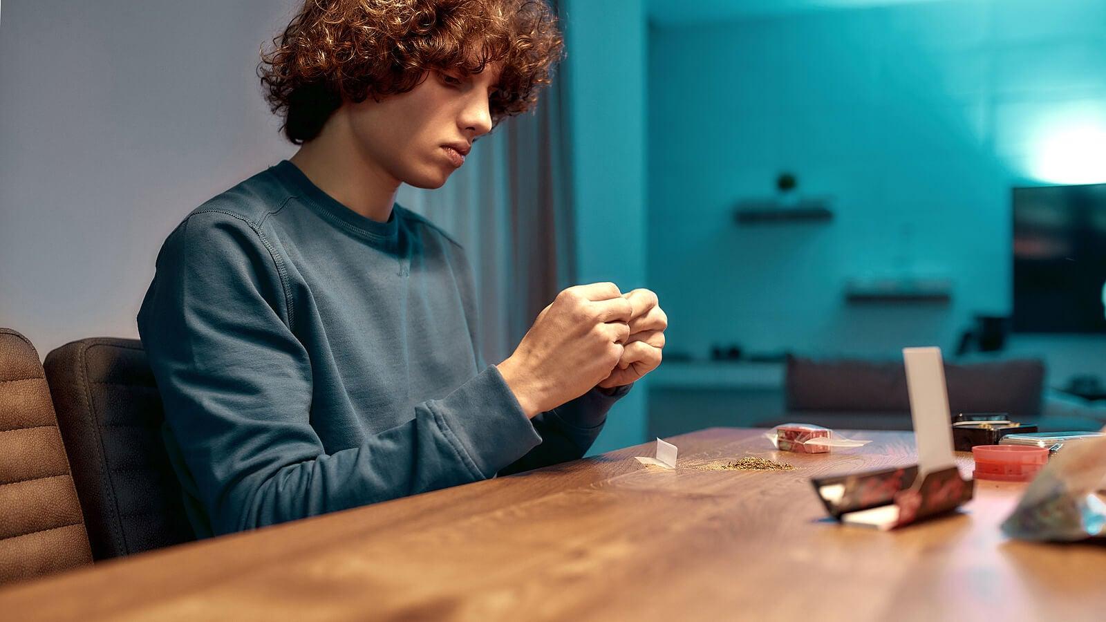 Chico adolescente haciéndose un porro de cannabis.