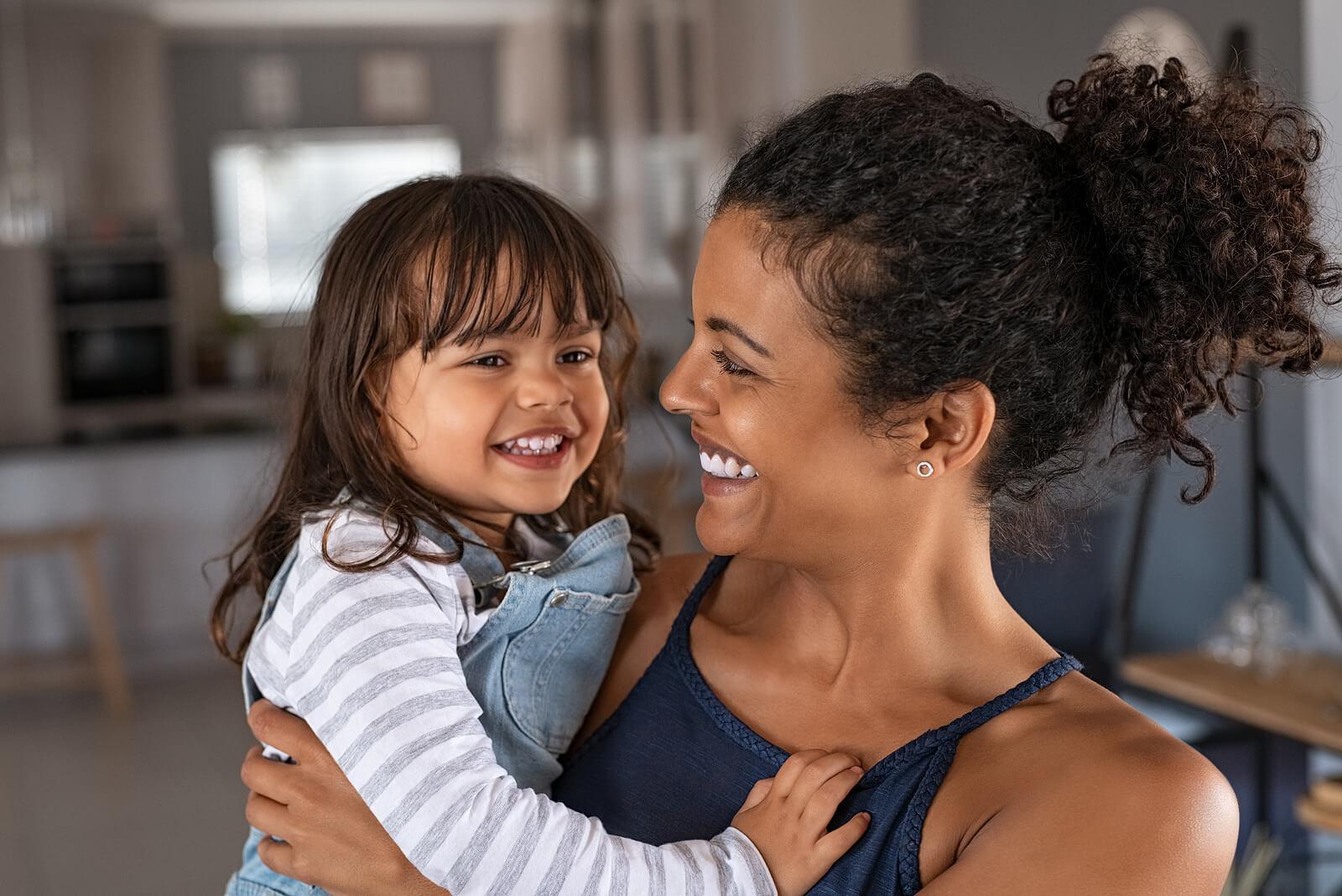 Madre abrazando a su hija con una sonrisa de felicidad.