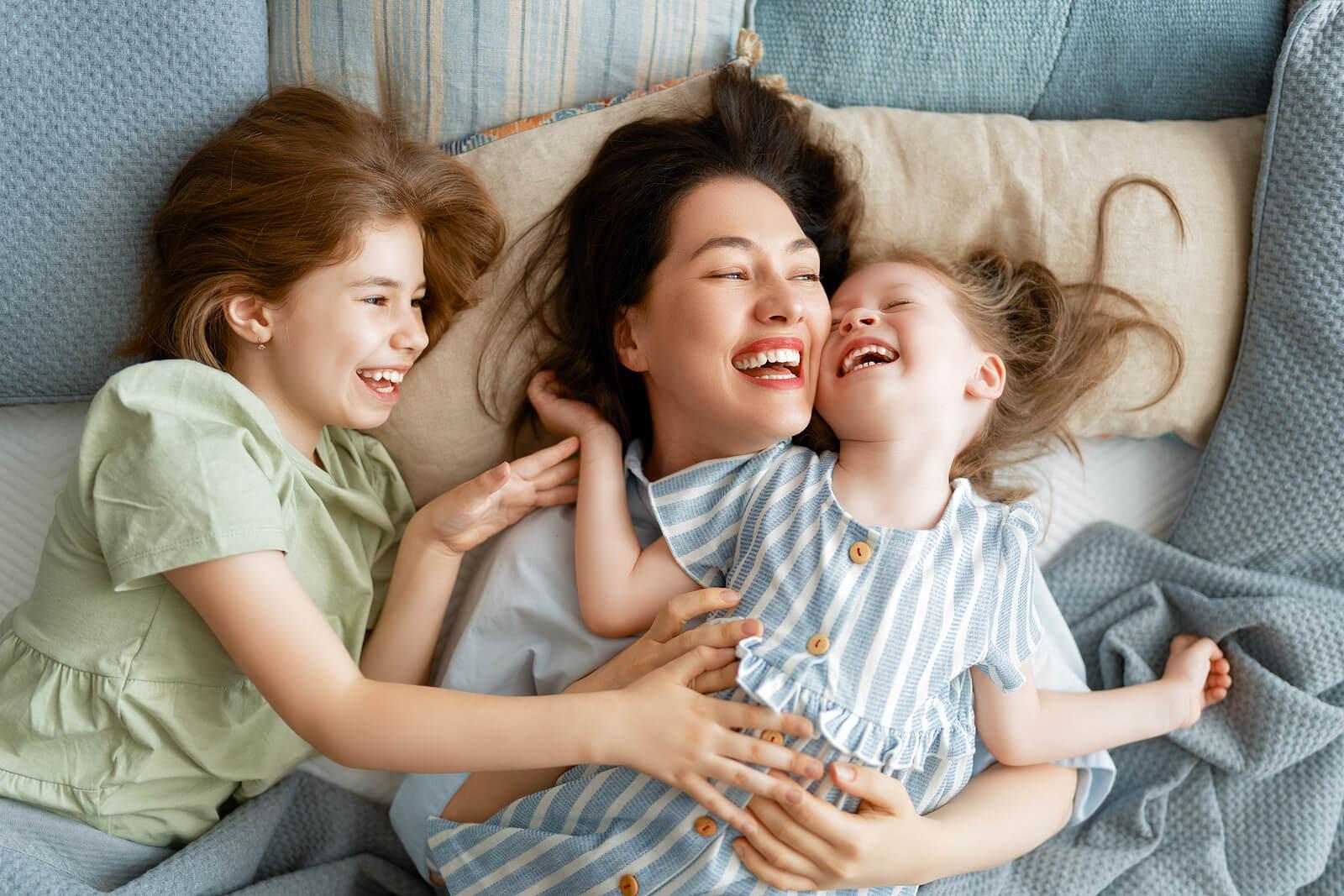 Madre disfrutando con sus hijas mientras se ríen en la diferentes etapas del humor infantil.