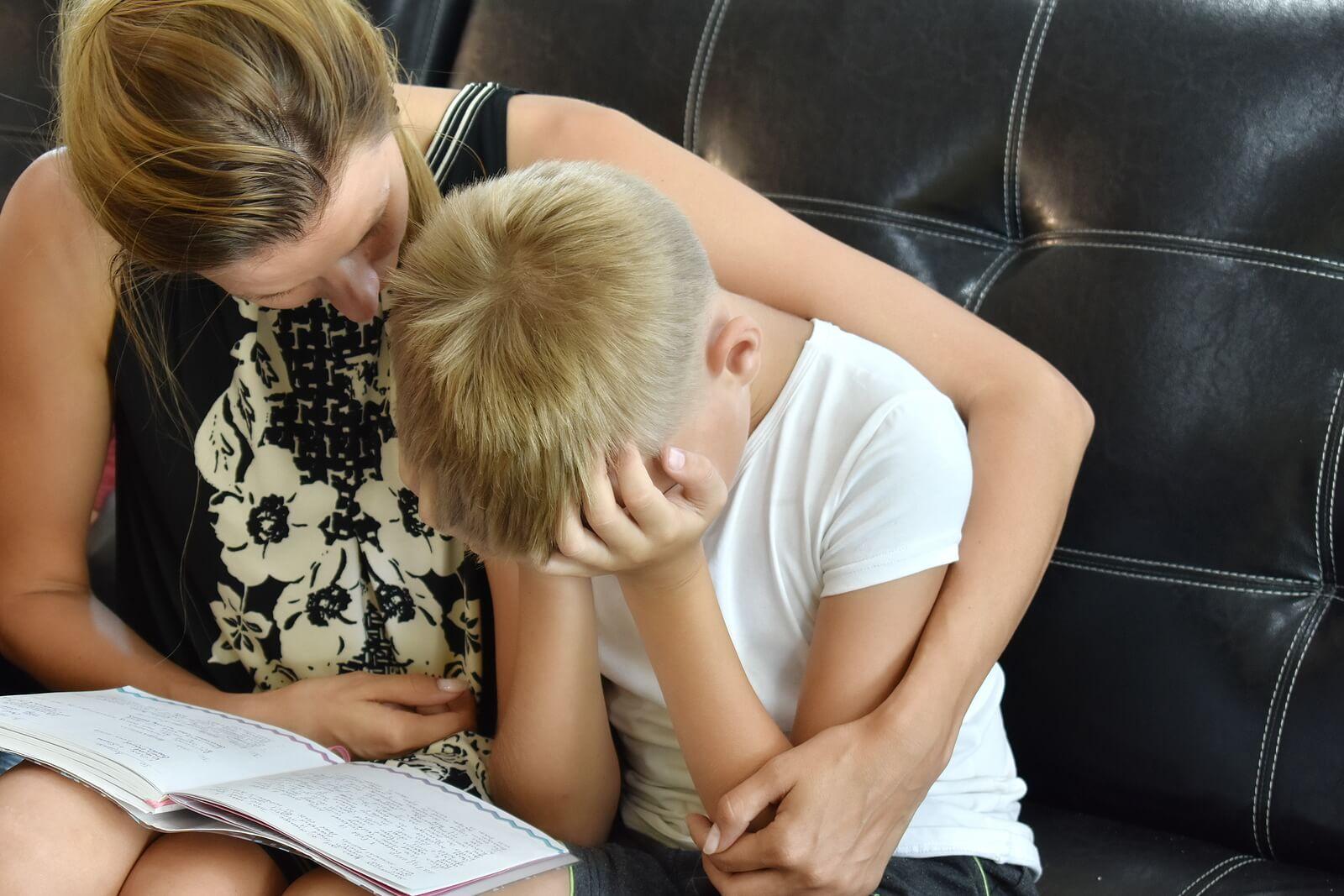 """Madre consolando a su hijo mientras le da un abrazo porque tiene en mente la frase: """"cuando llores, te abrazaré""""."""