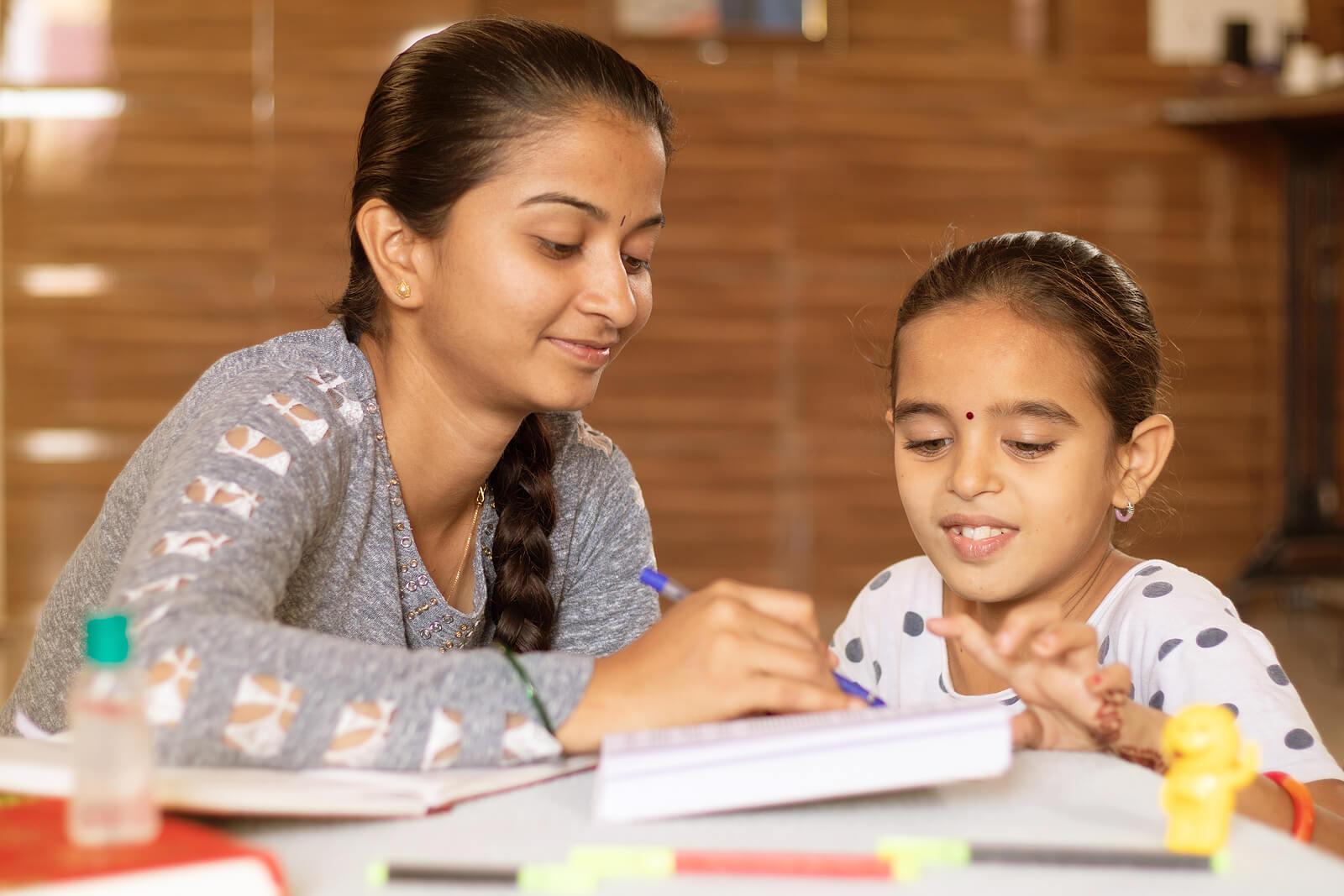Madre con su hija practicando el homeschooling.