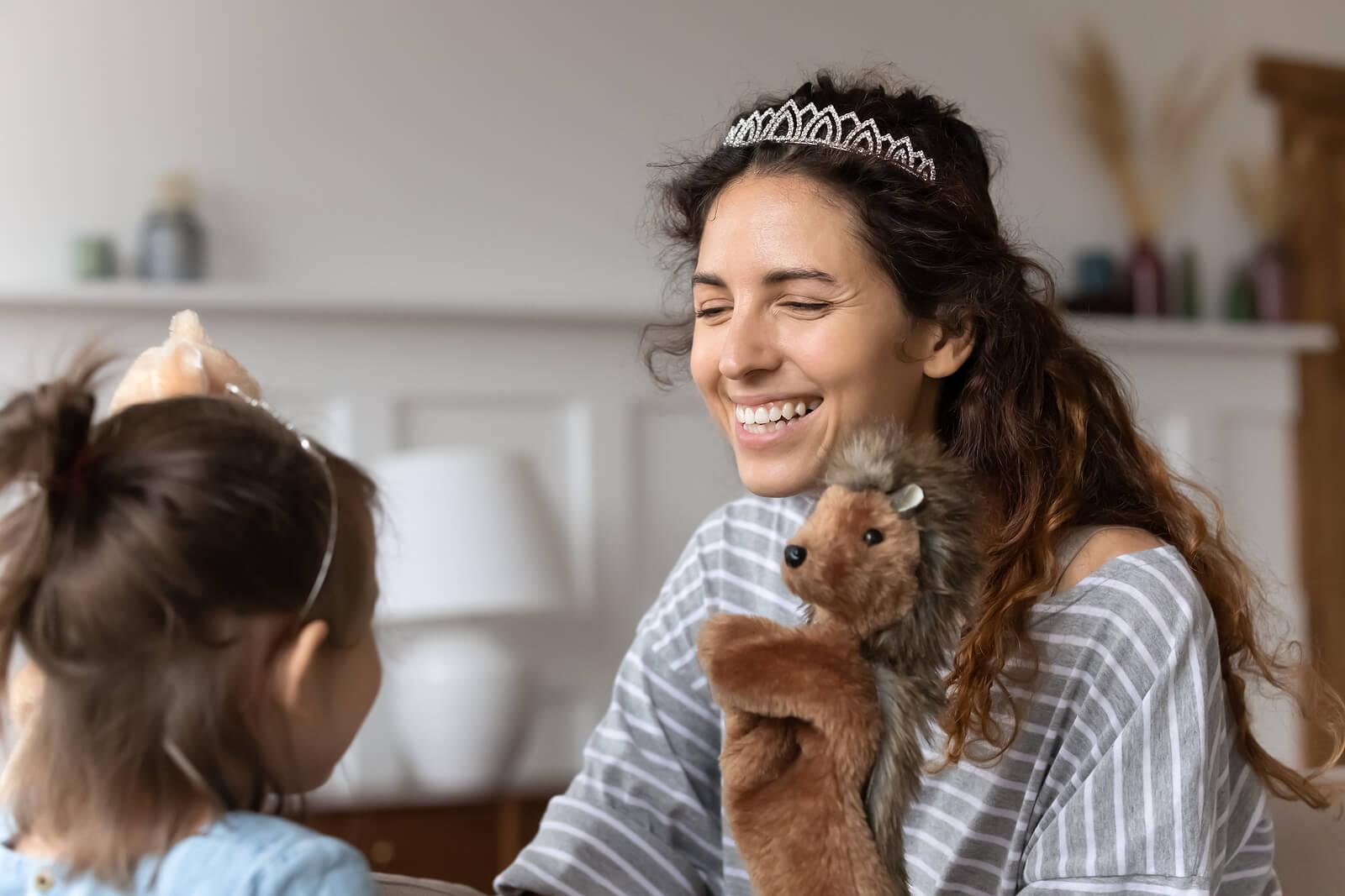 Madre e hija jugando con marionetas y disfrazadas de princesas.