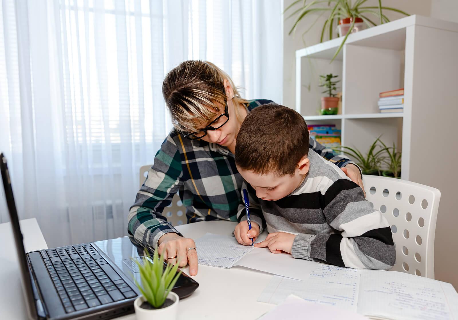 Madre e hijo estudiando en casa gracias al homeschooling.