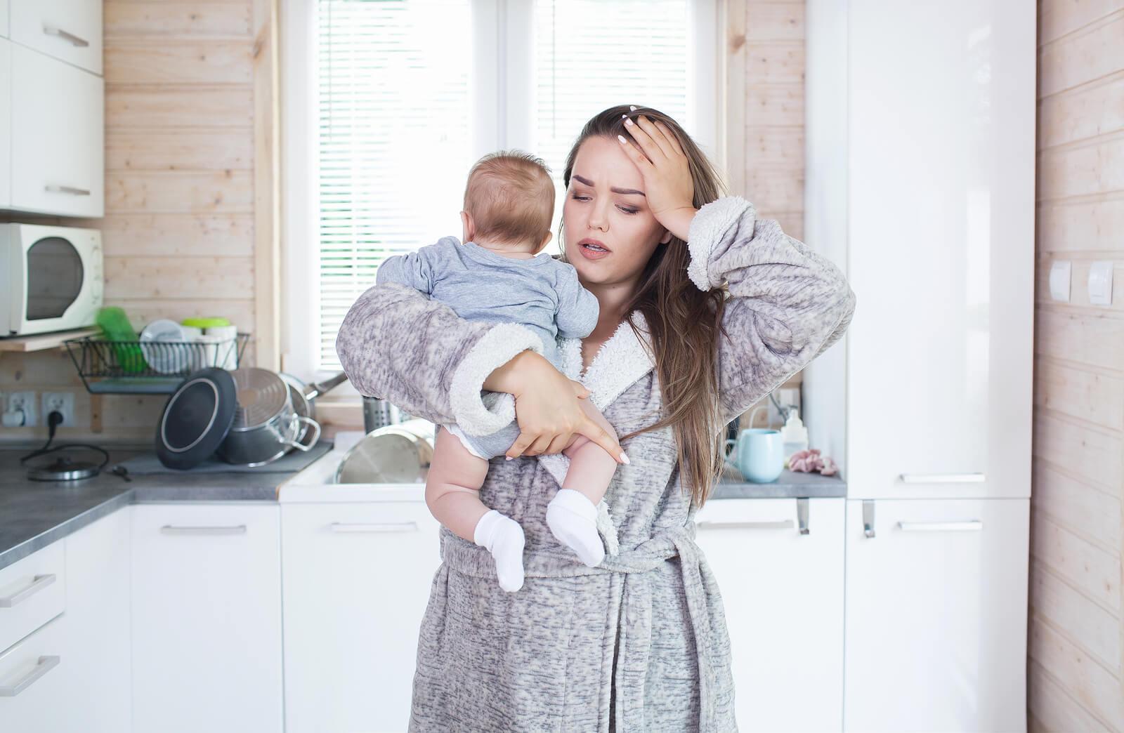 Mamá con su recién nacido en brazos desesperada.