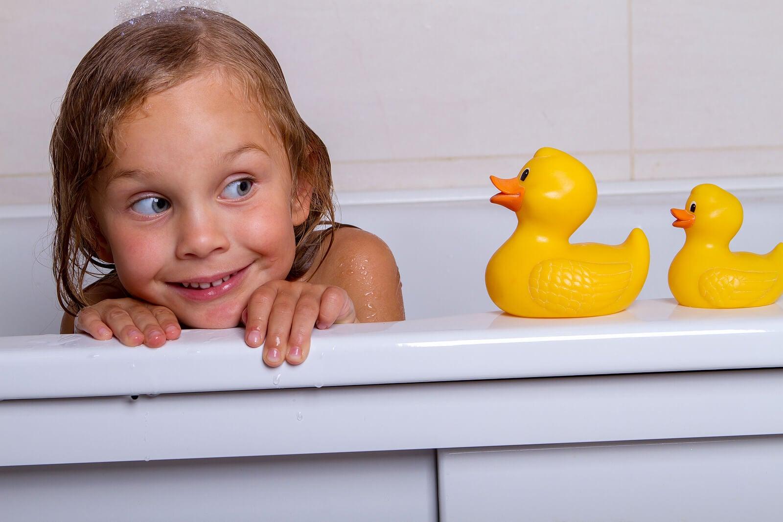 Niña jugando con los patitos de goma en la bañera.