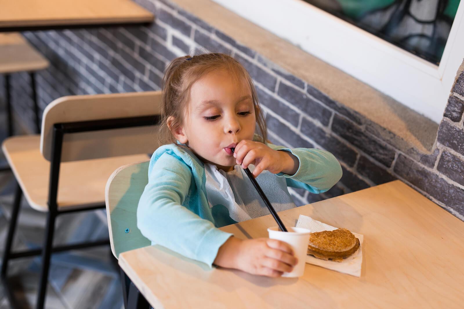 Niña merendando chocolate sin saber el riesgo de comer entre horas en niños.