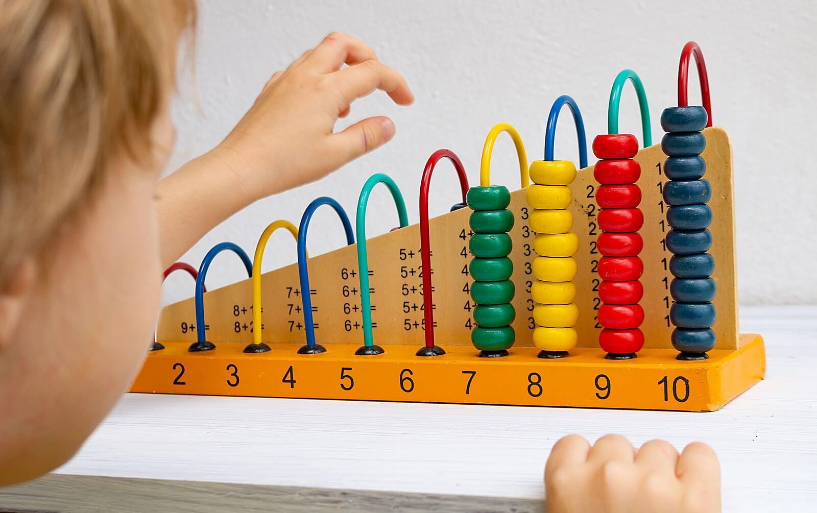 Niño aprendiendo matemáticas tempranas con un ábaco gracias al método Montessori.