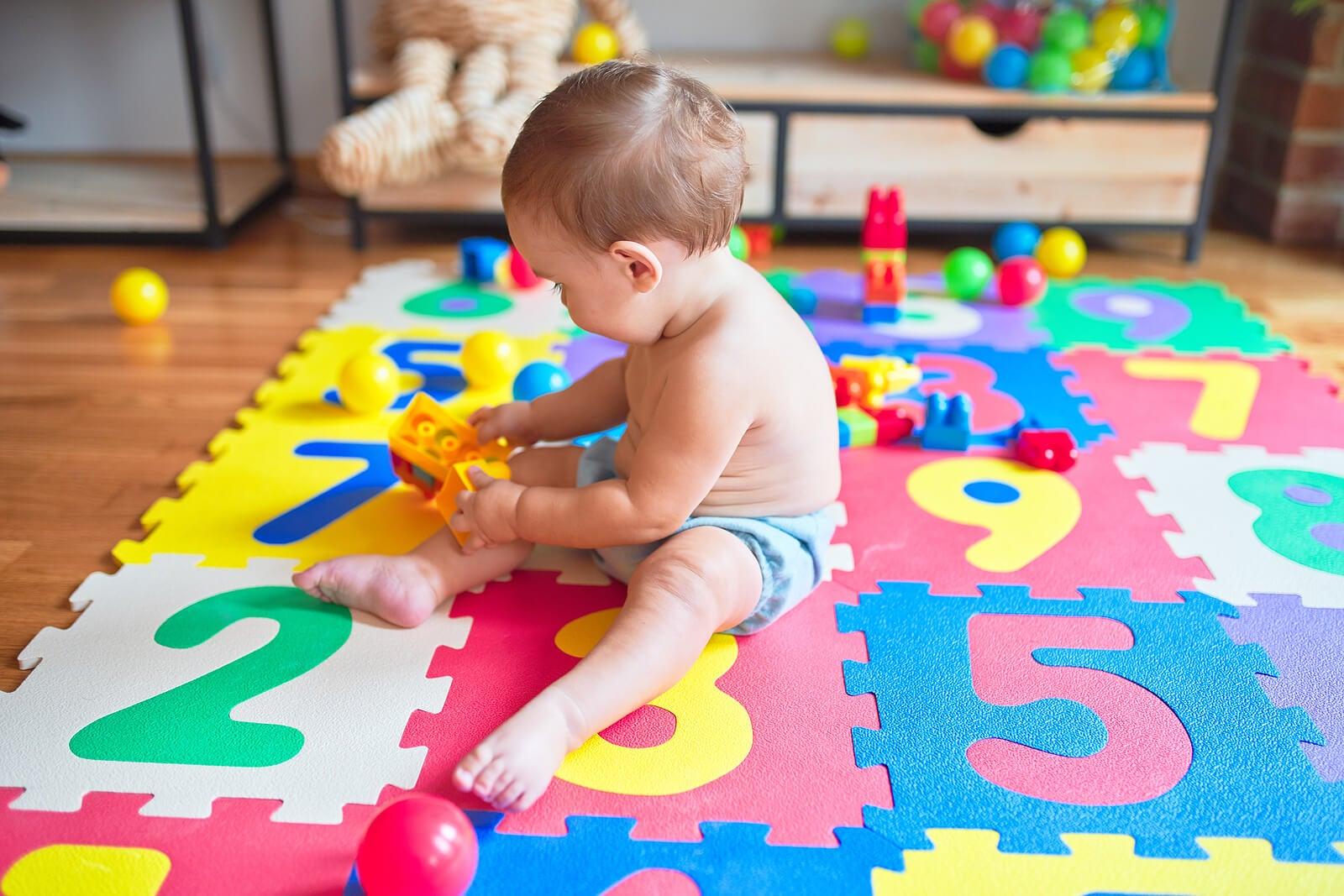 Niño en una alfombra con rompecabezas.