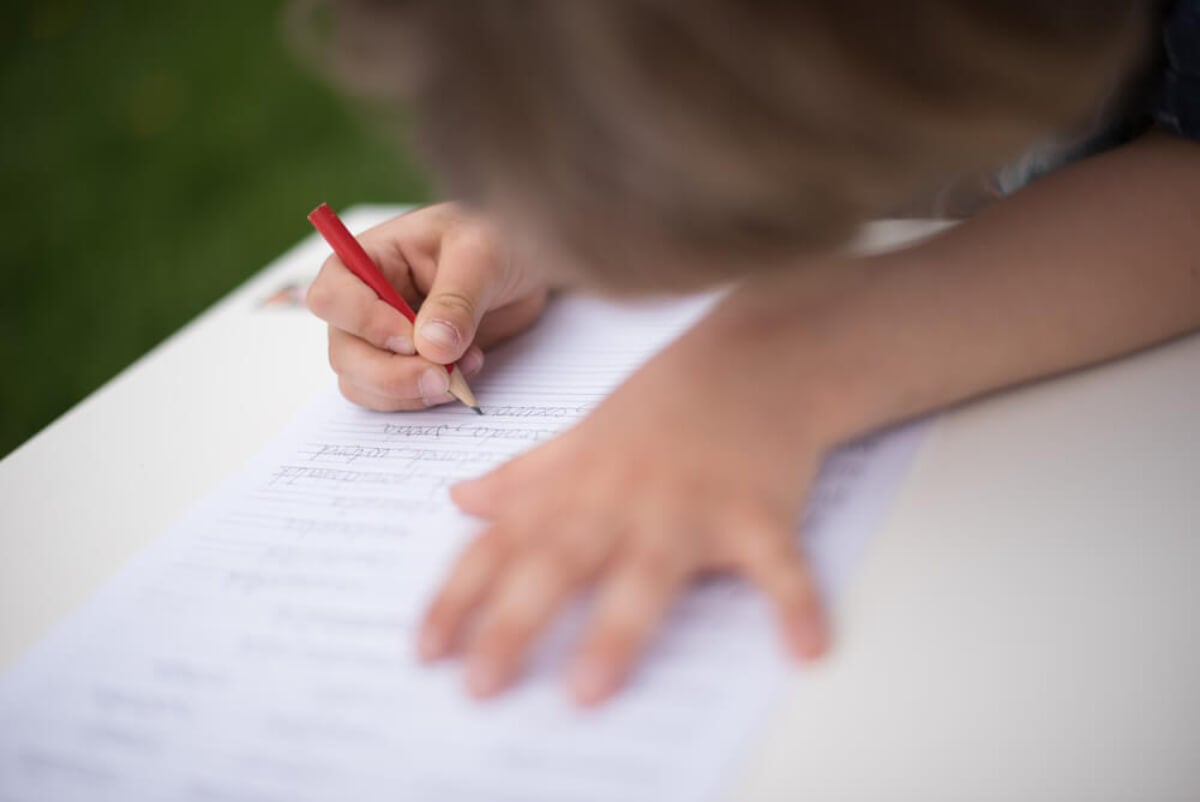 Niño aprendiendo a escribir gracias a la pauta Montessori.