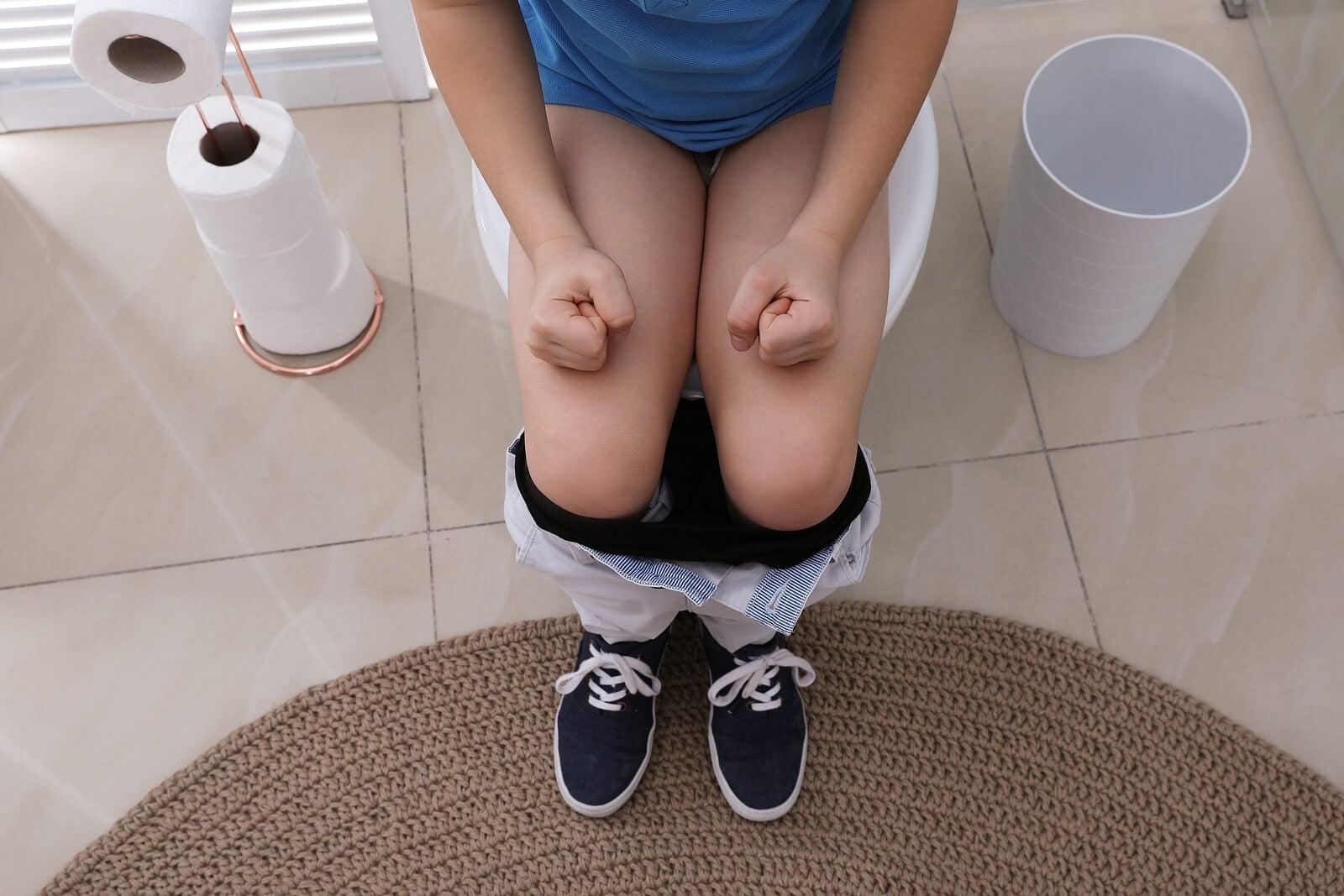 Niño con estreñimiento en el baño apretando los puños.