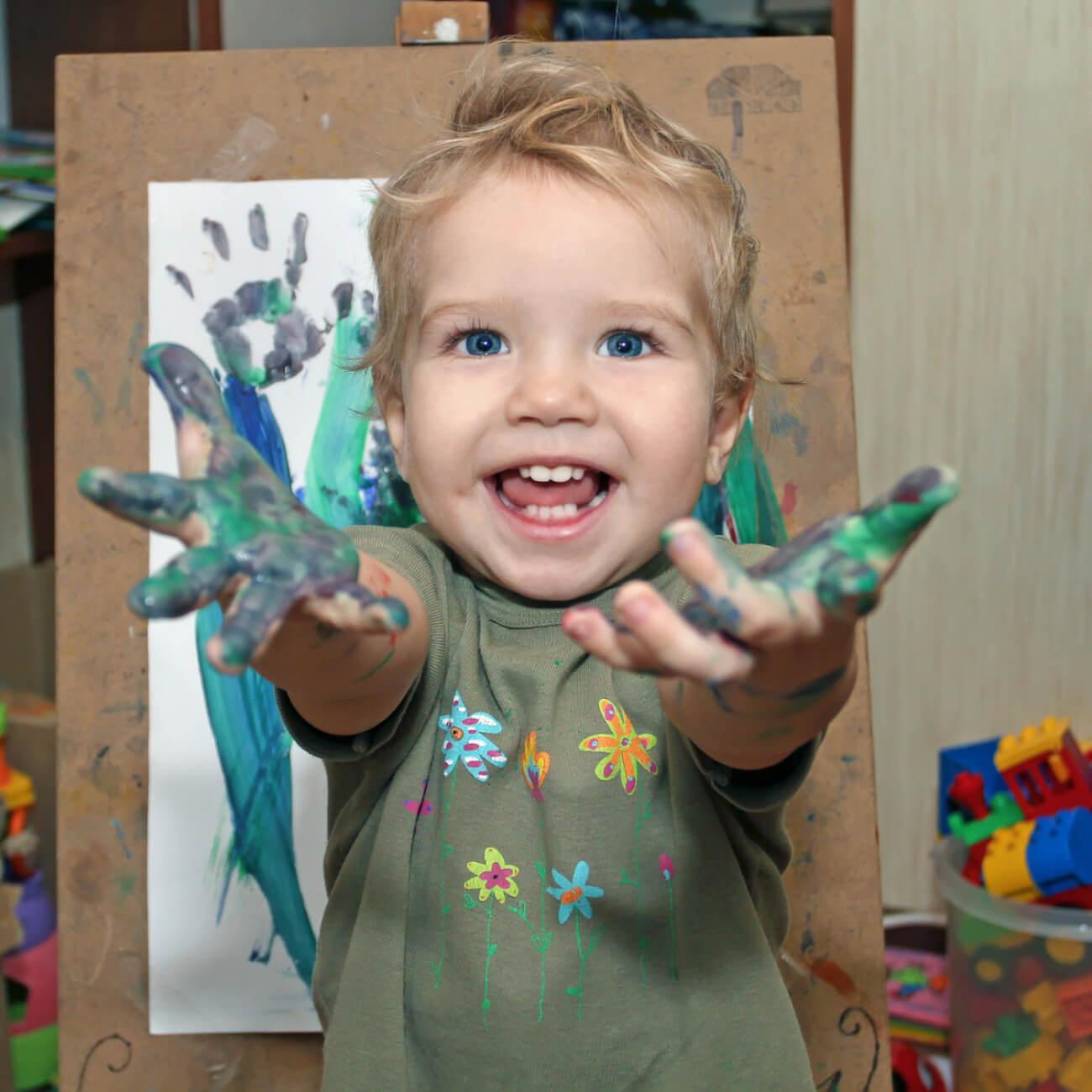 Niño con las manos llenas de pintura.
