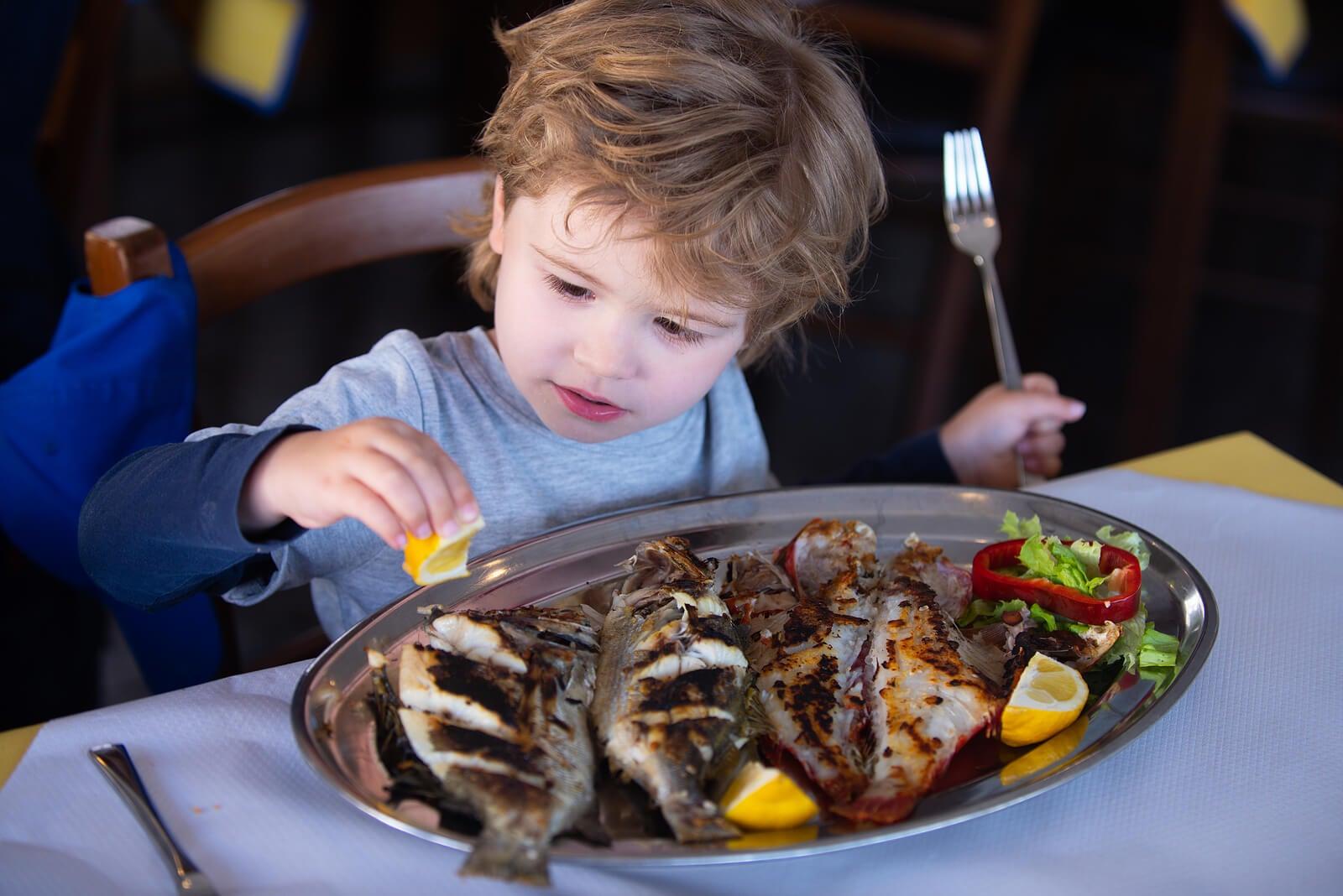 Niño comiendo pescado porque es muy importante en la alimentación infantil.