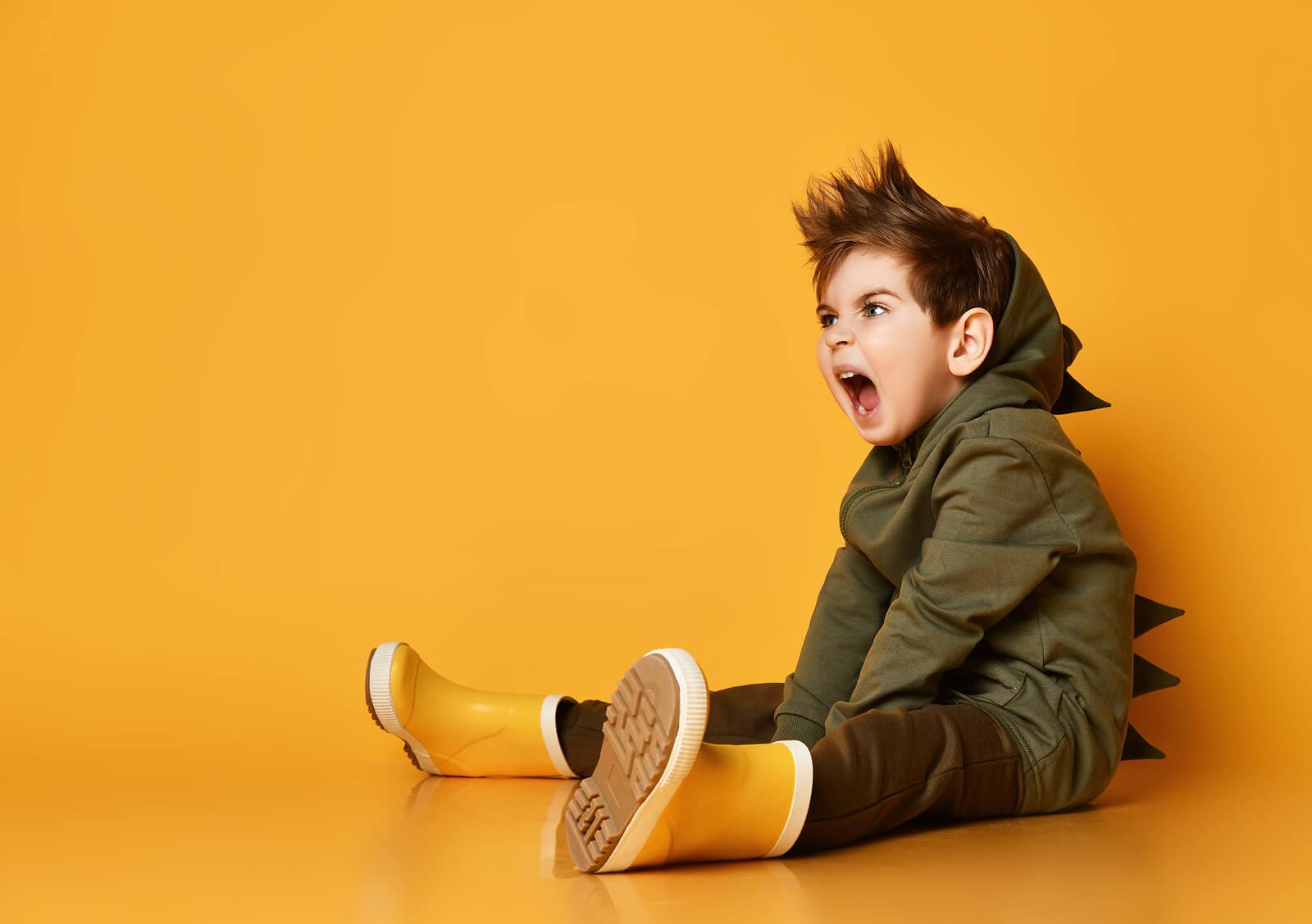 Niño chillando porque sus padres intentar evitar que insulte.