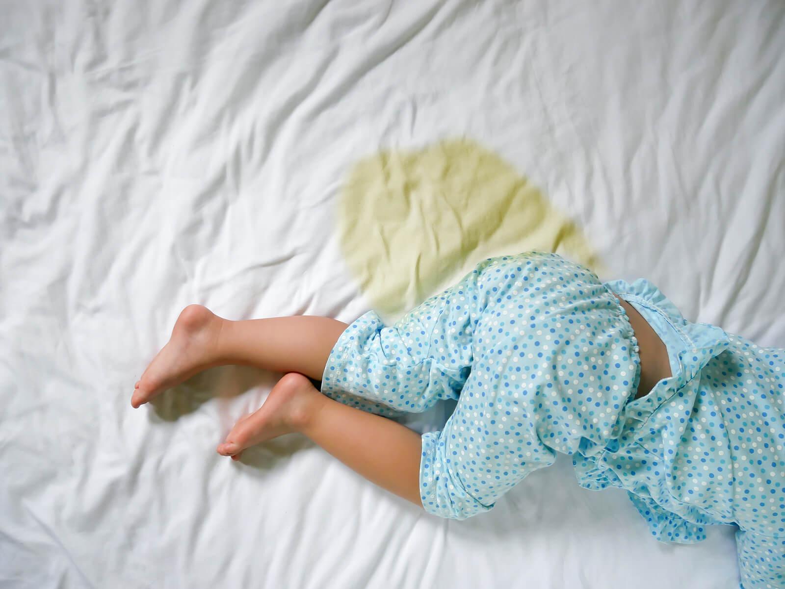 Niño con las sábanas mojadas porque se ha hecho pis en la cama por la noche.