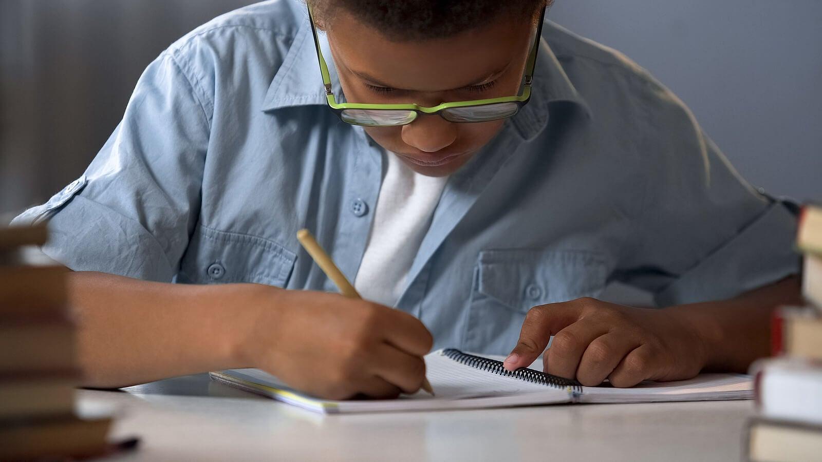 Niño con disortografía escribiendo en un cuaderno.