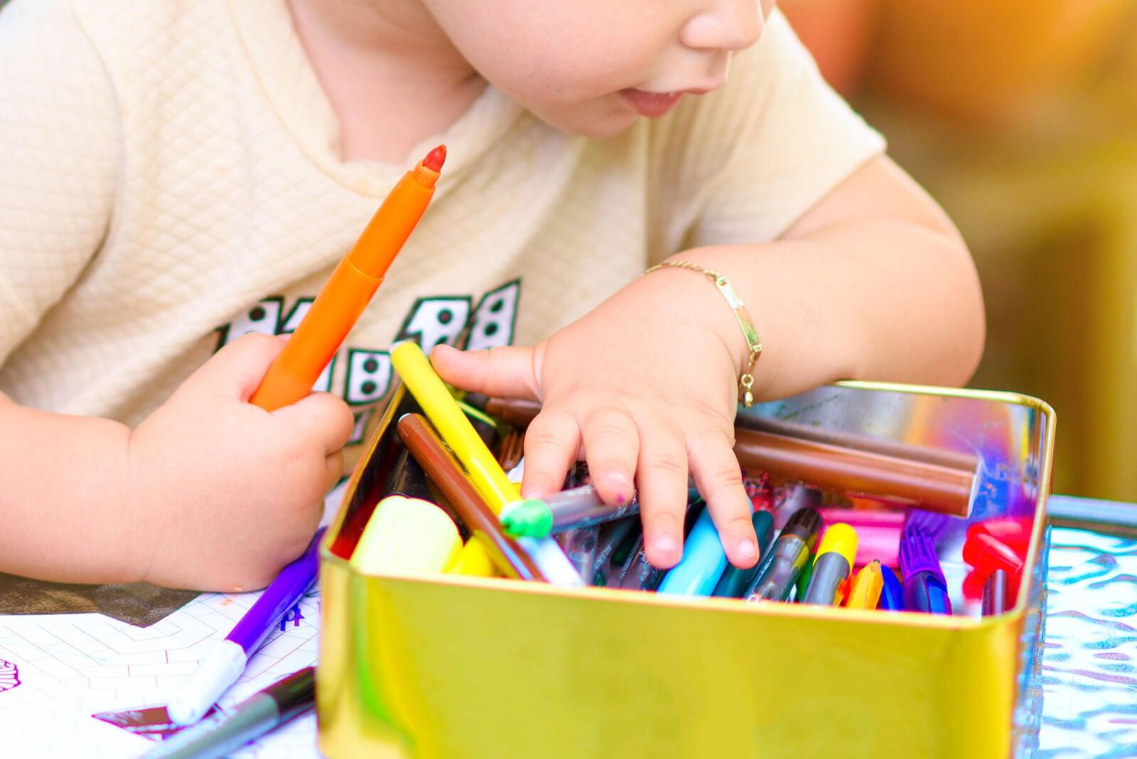 Niño haciendo un dibujo con rotuladores de colores.