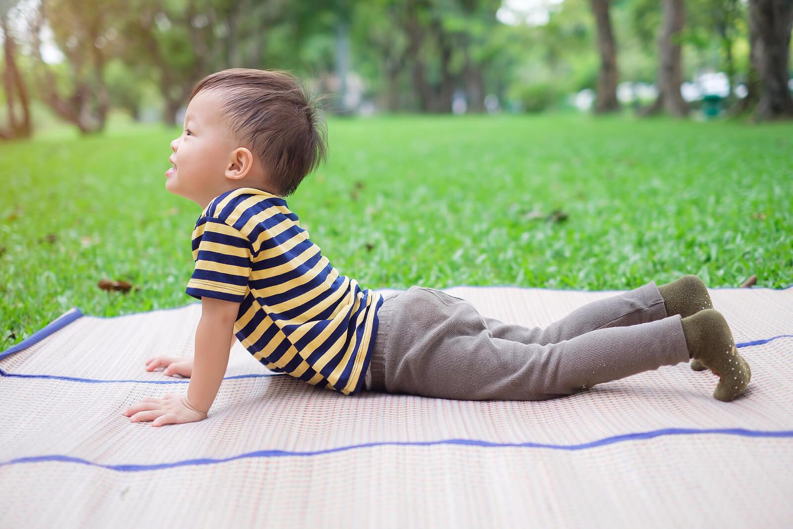 Niño tumbado en el suelo haciendo la postura del perro boca arriba.