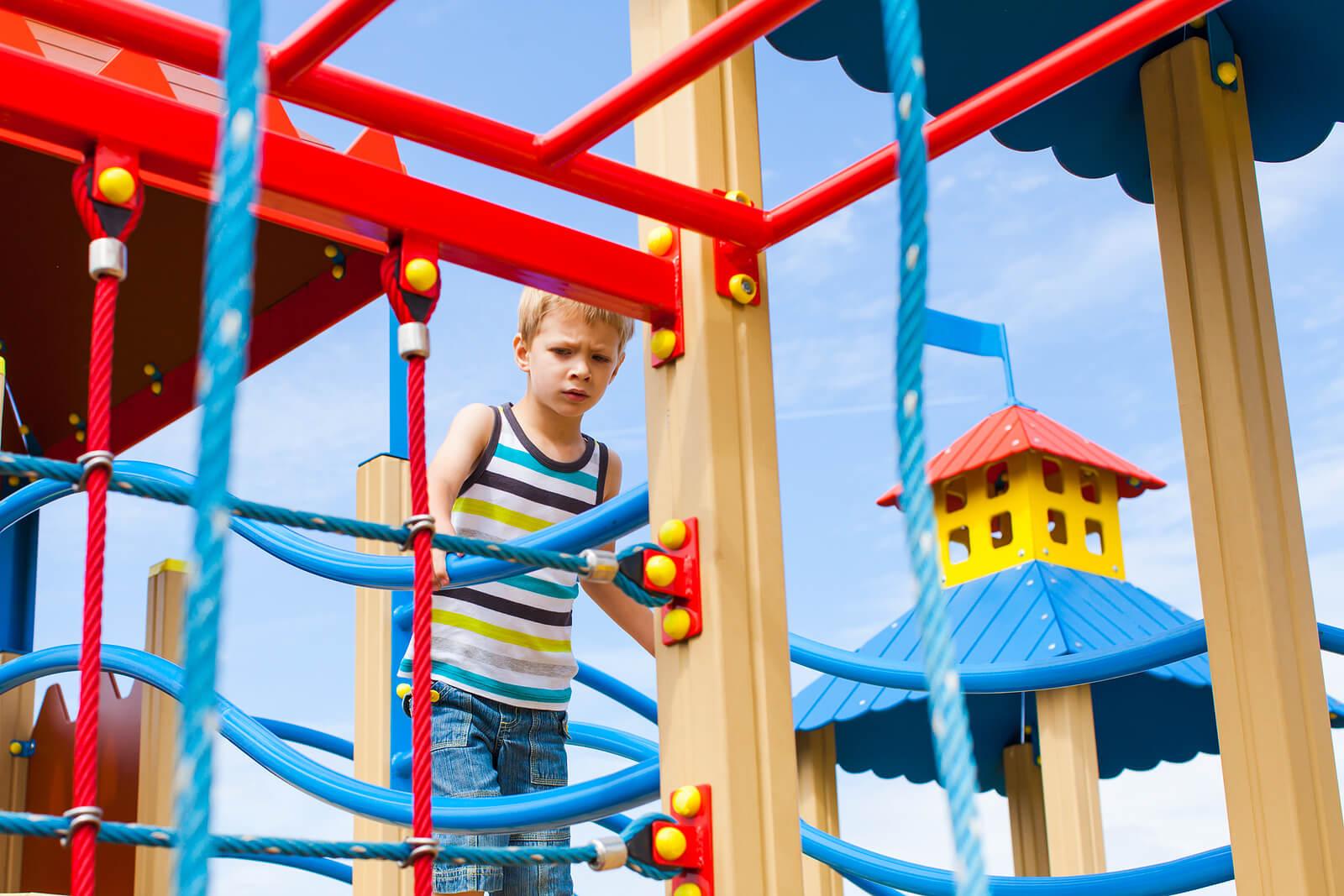 Niño jugando en el parque con miedo a las alturas.