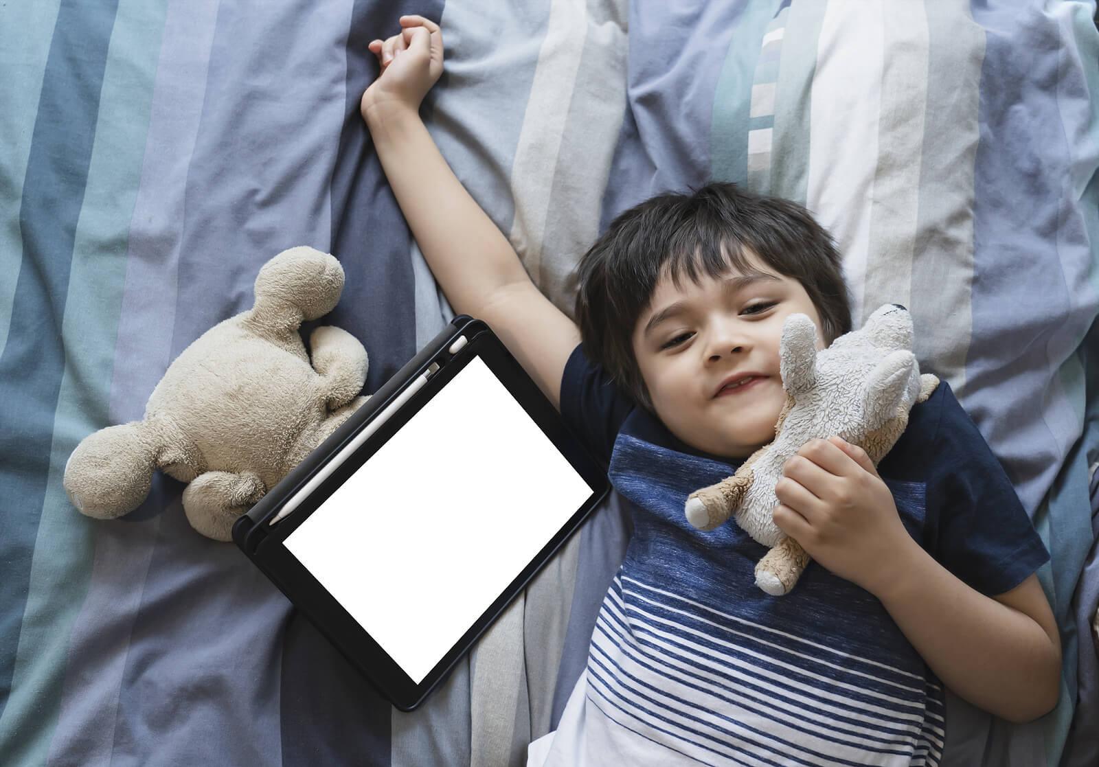 Niño usando una tablet antes de dormir, uno de los errores que cometemos al acostar al niño.